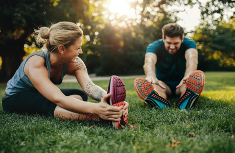 Man and woman in workout clothes stretch while sitting on grass