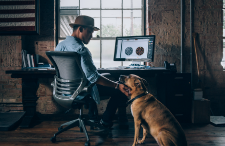 Man sitting in front of computer while petting dog