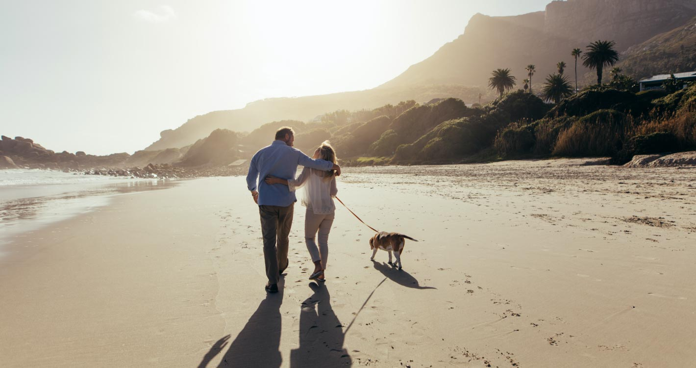 Couple walking down along the beach
