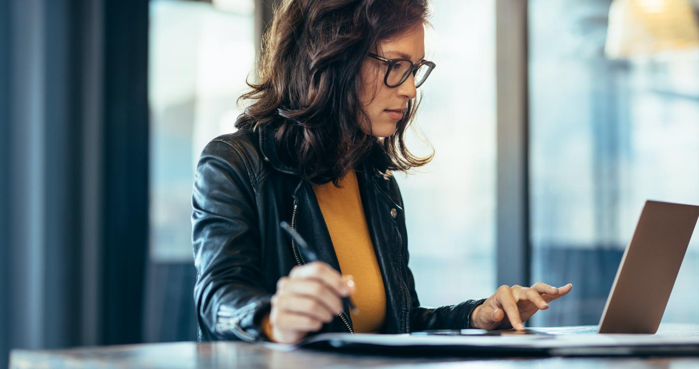 Woman focuses while working on laptop