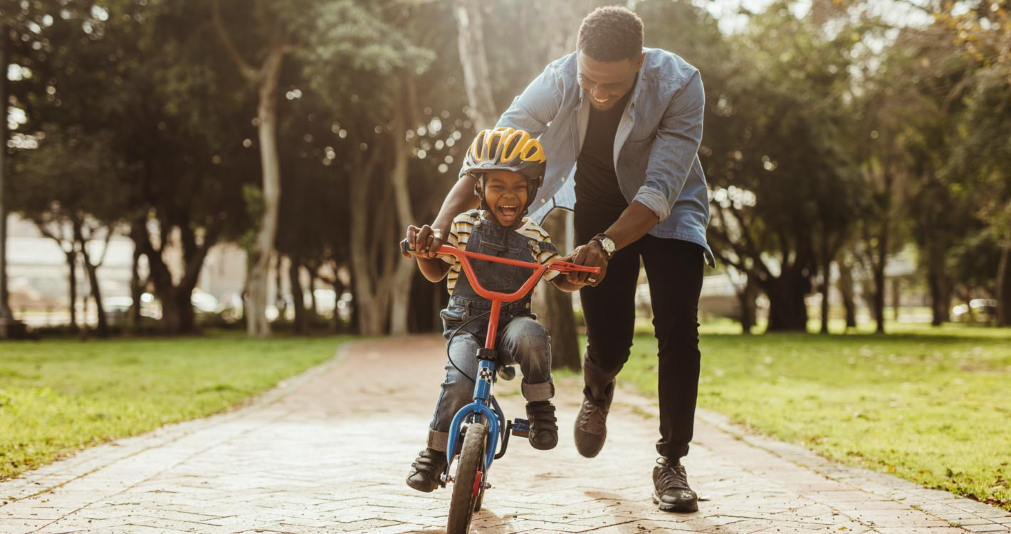 Dad teaching child how to ride a bicycle