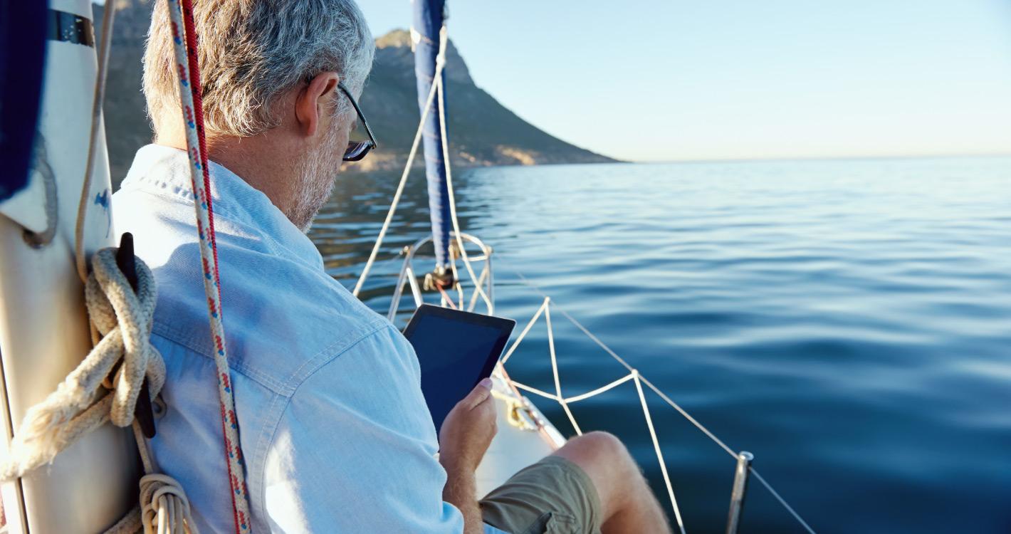 Closeup of older man using ipad while sitting on boat