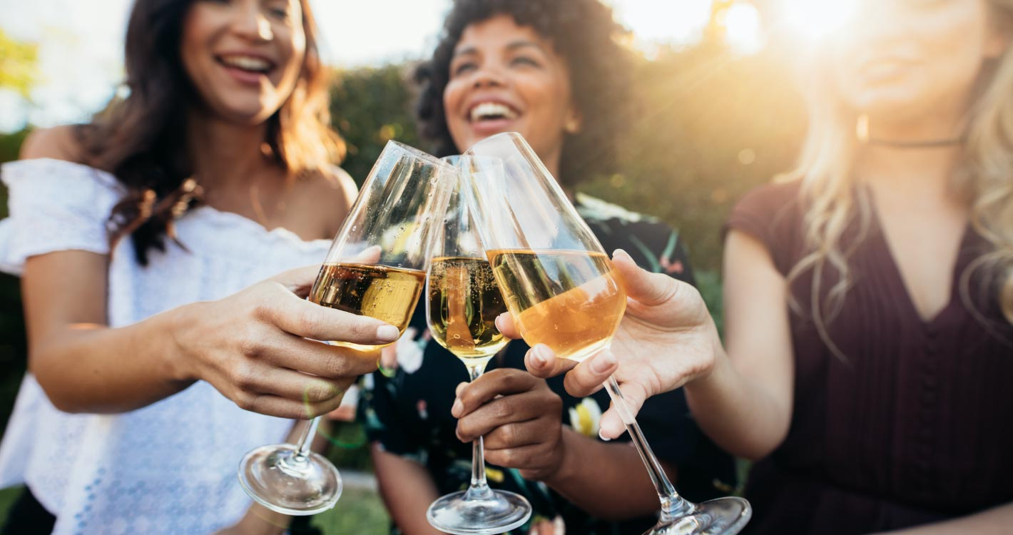 Three woman clicking champagne glasses together while smiling