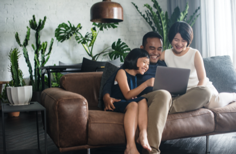 Family sitting on couch while looking at laptop